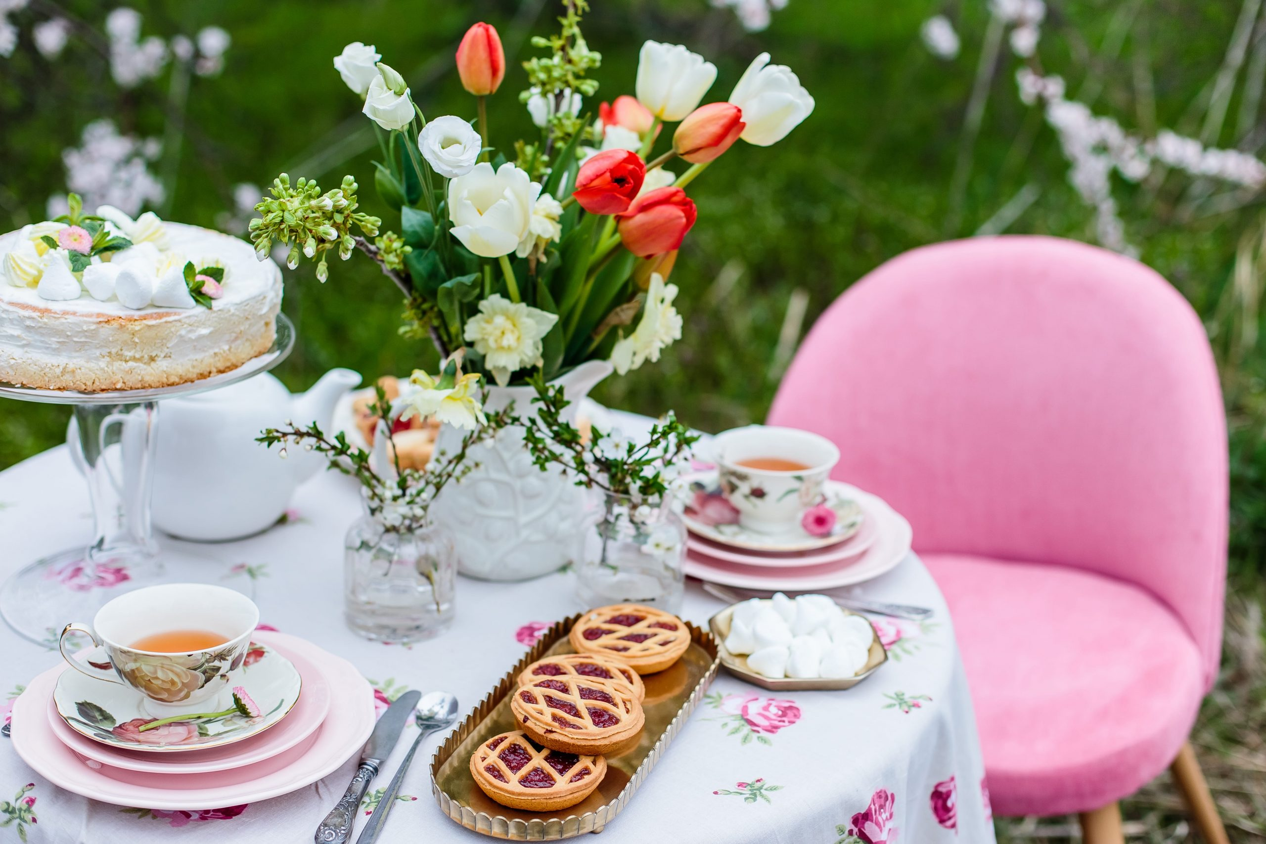 Tea time with cake and cookies in the spring garden outdoors. The table is covered with a floral tablecloth. In english style